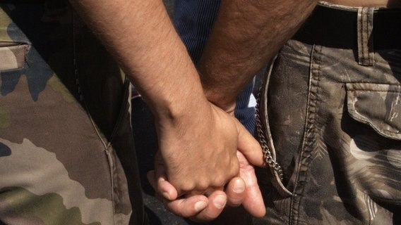 Gay_couple_from_back_hand_holding_on_csd_2006_berlin_-_make_love_not_war2
