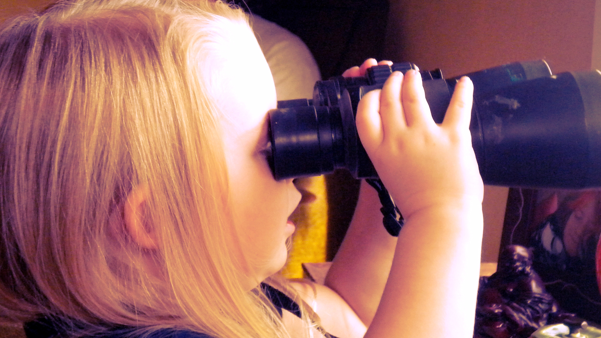 A child looks through binoculars