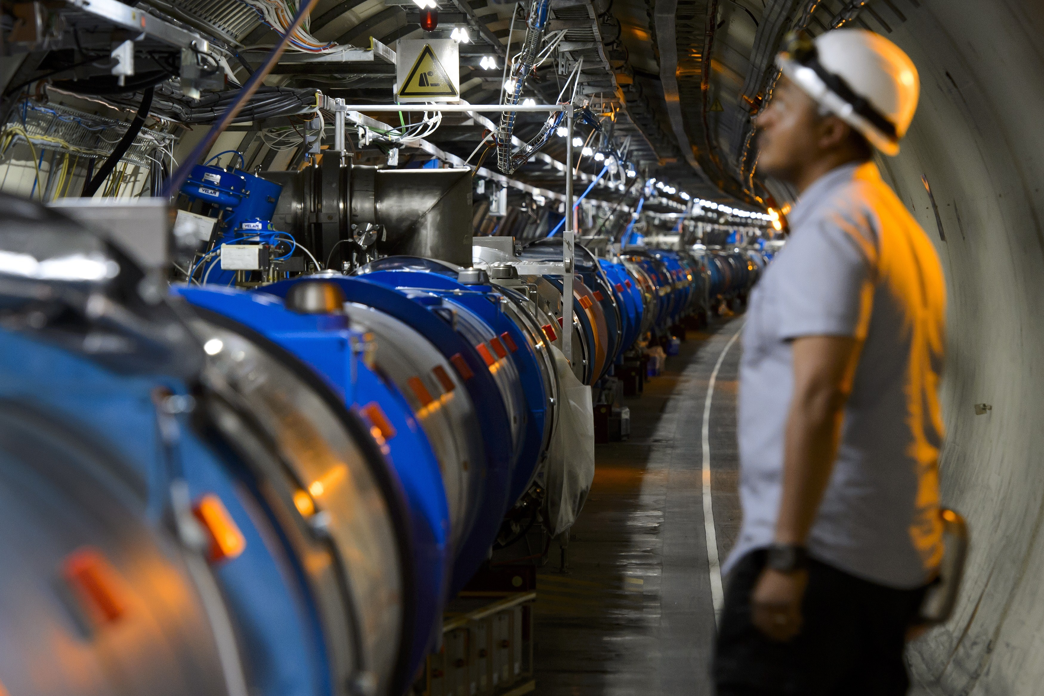 A scientist looks up at a section of the Large Hadron Collider.