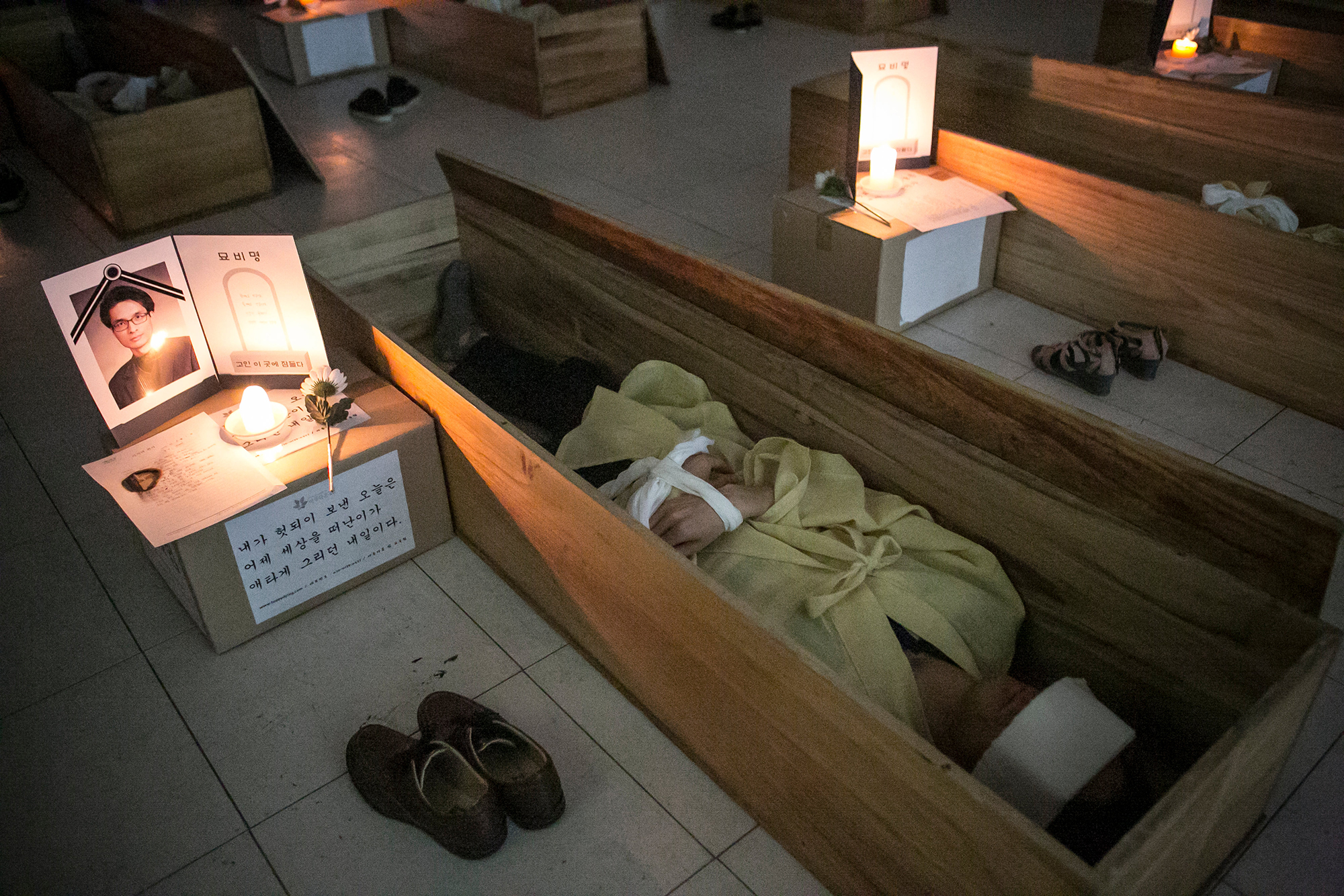 Participants wearing linen shrouds meditate and reflect on their lives as they lie down in a coffin during a 'Death Experience/Fake Funeral' session