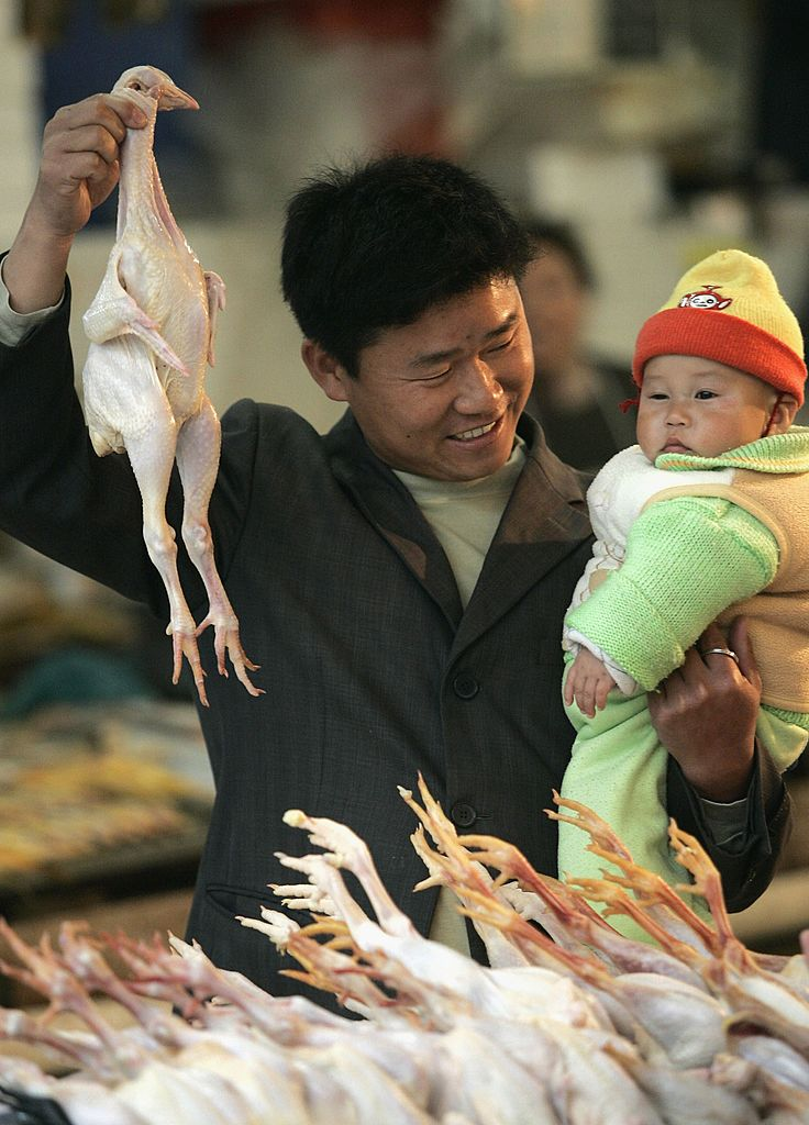 Man holding whole dead chicken with head (Credit: Getty Images)