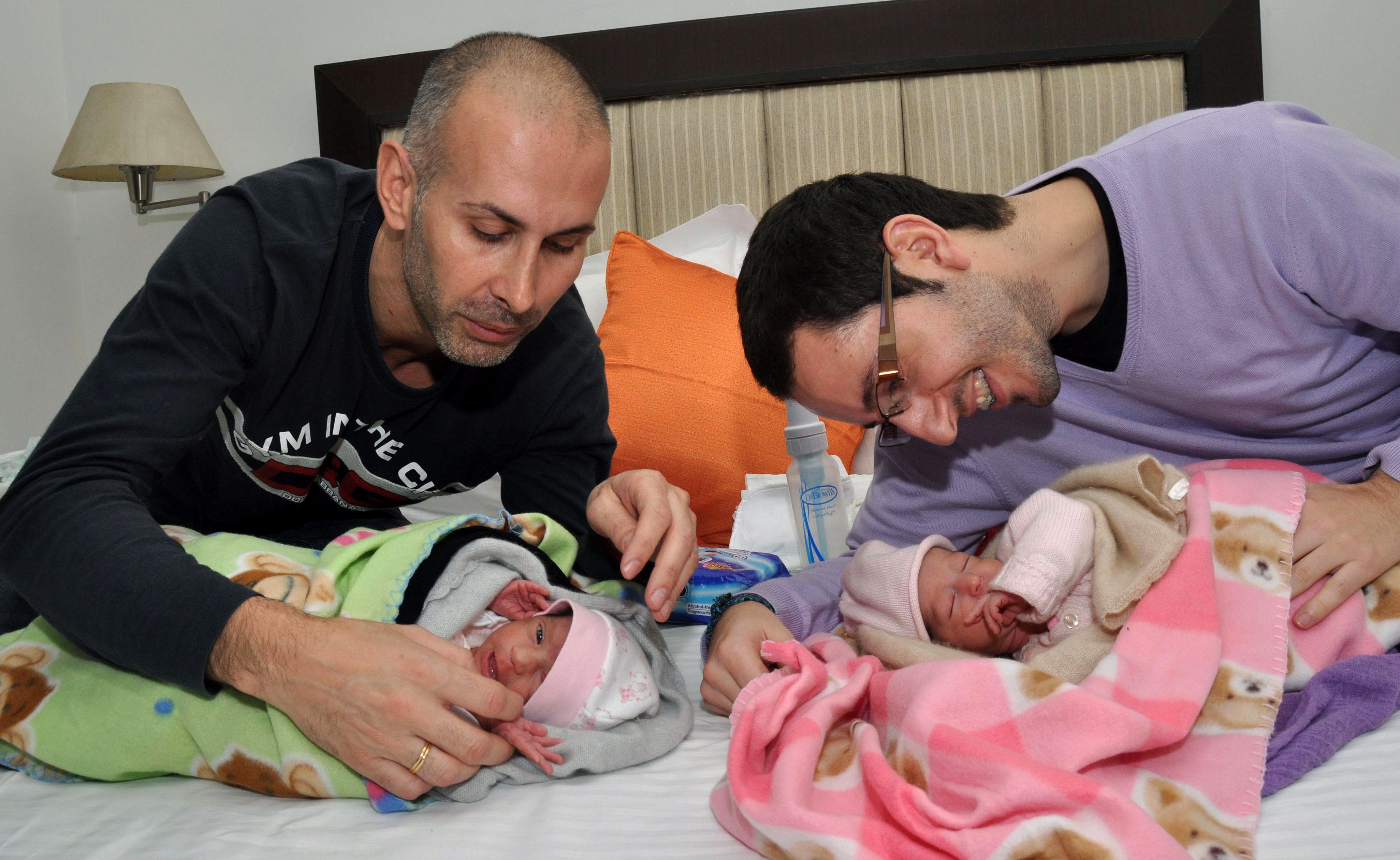 In this photograph taken on February 17, 2011, Spanish couple Mauro (L) and Juan Carlos embrace their new born twin girls at a hospital in New Delhi, after an Indian surrogate mother gave birth to the children.