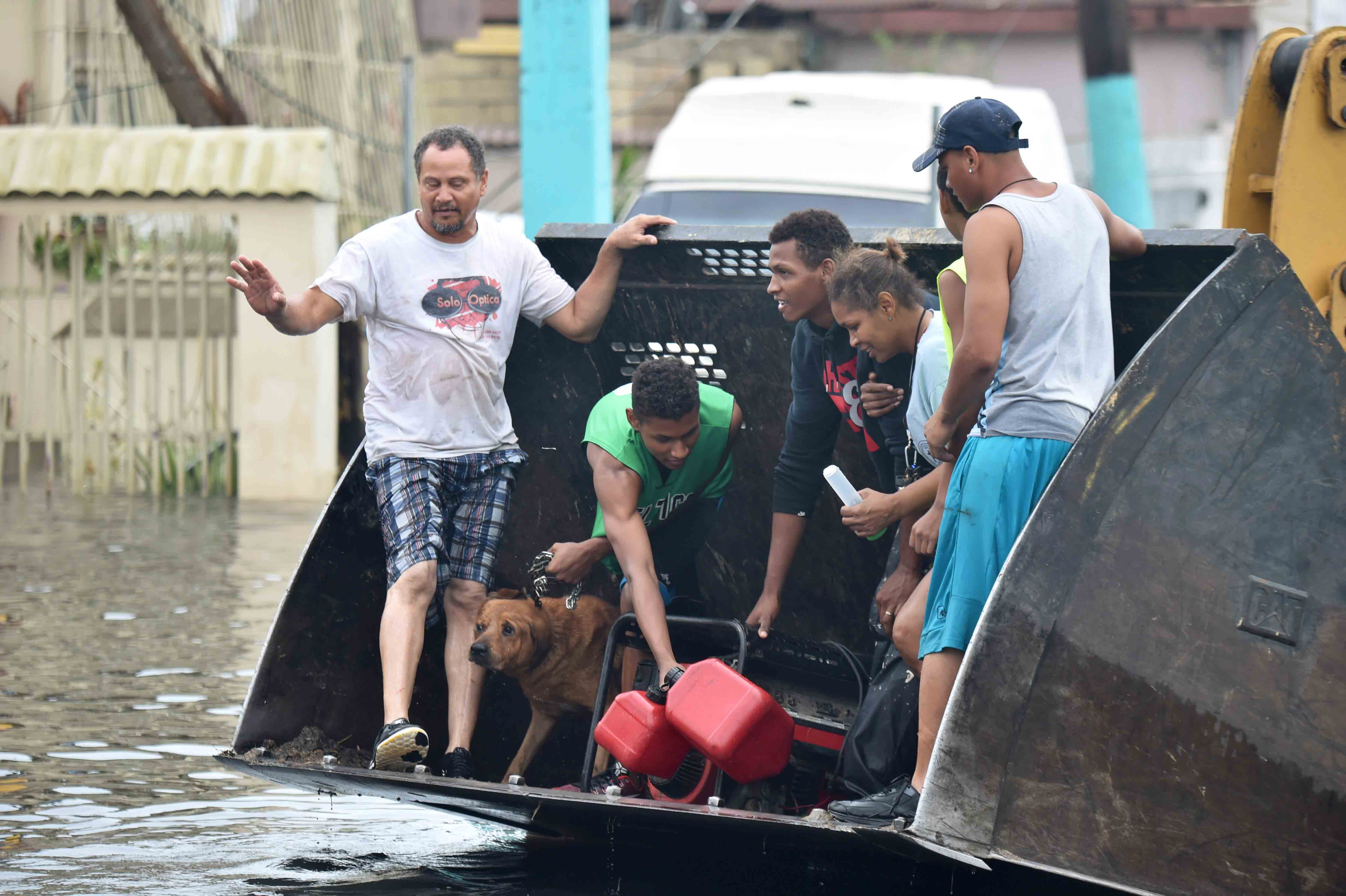 People are transported down a road flooded by Hurricane Maria in Juana Matos, Catanon, Puerto Rico.