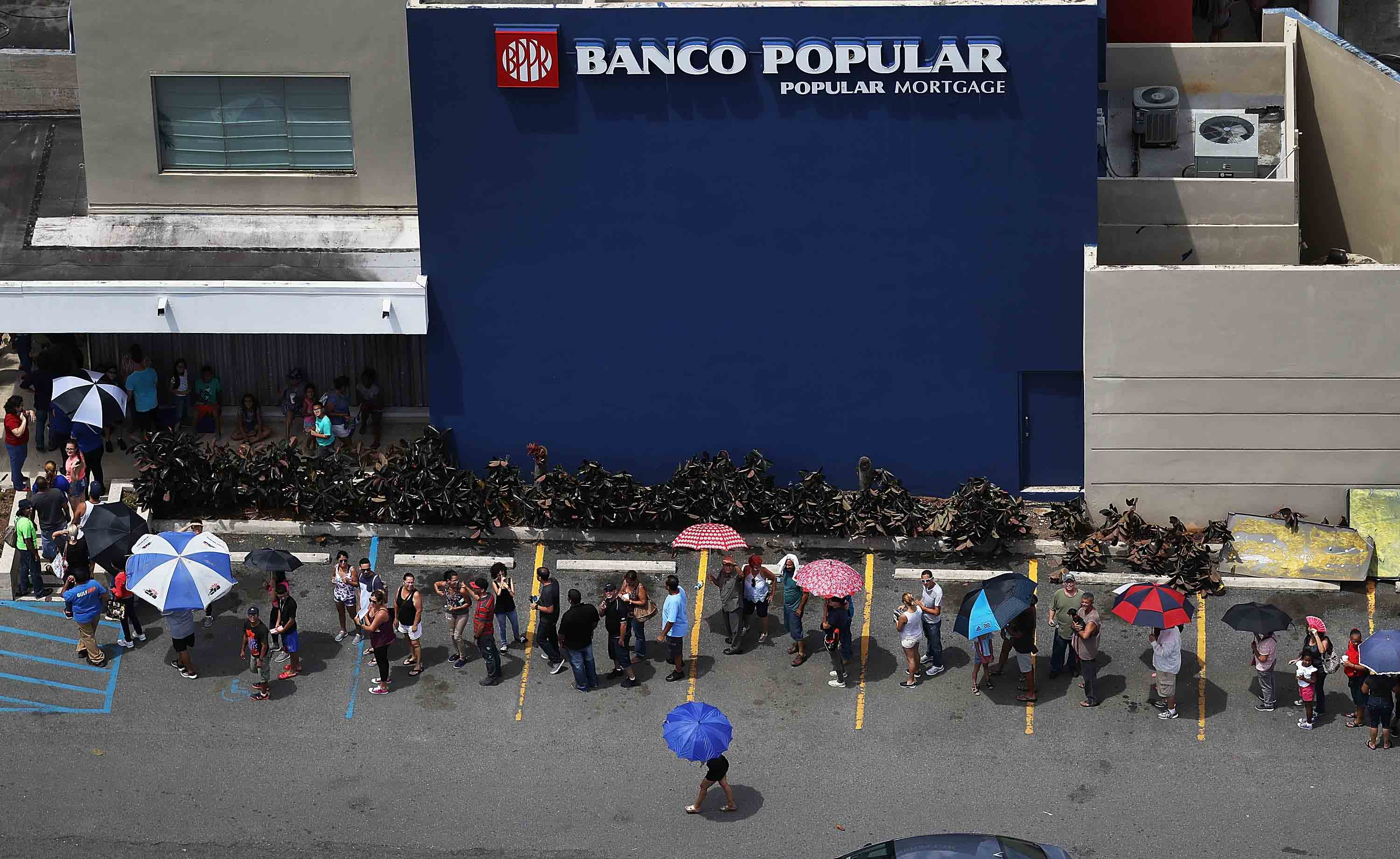People wait in line at a bank as they deal with the aftermath of Hurricane Maria on September 25, 2017 in San Juan Puerto Rico.