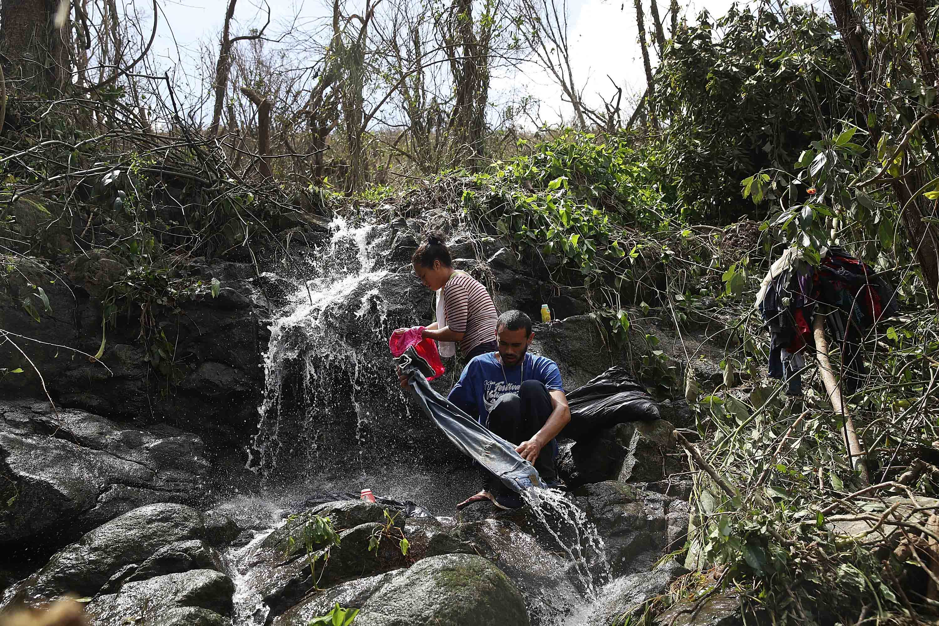 AIBONITO, PUERTO RICO - SEPTEMBER 24: Danalys Luna and Edgardo Feliciano wash their clothes in a stream as people wait for the electrical and water grids to be repaired.