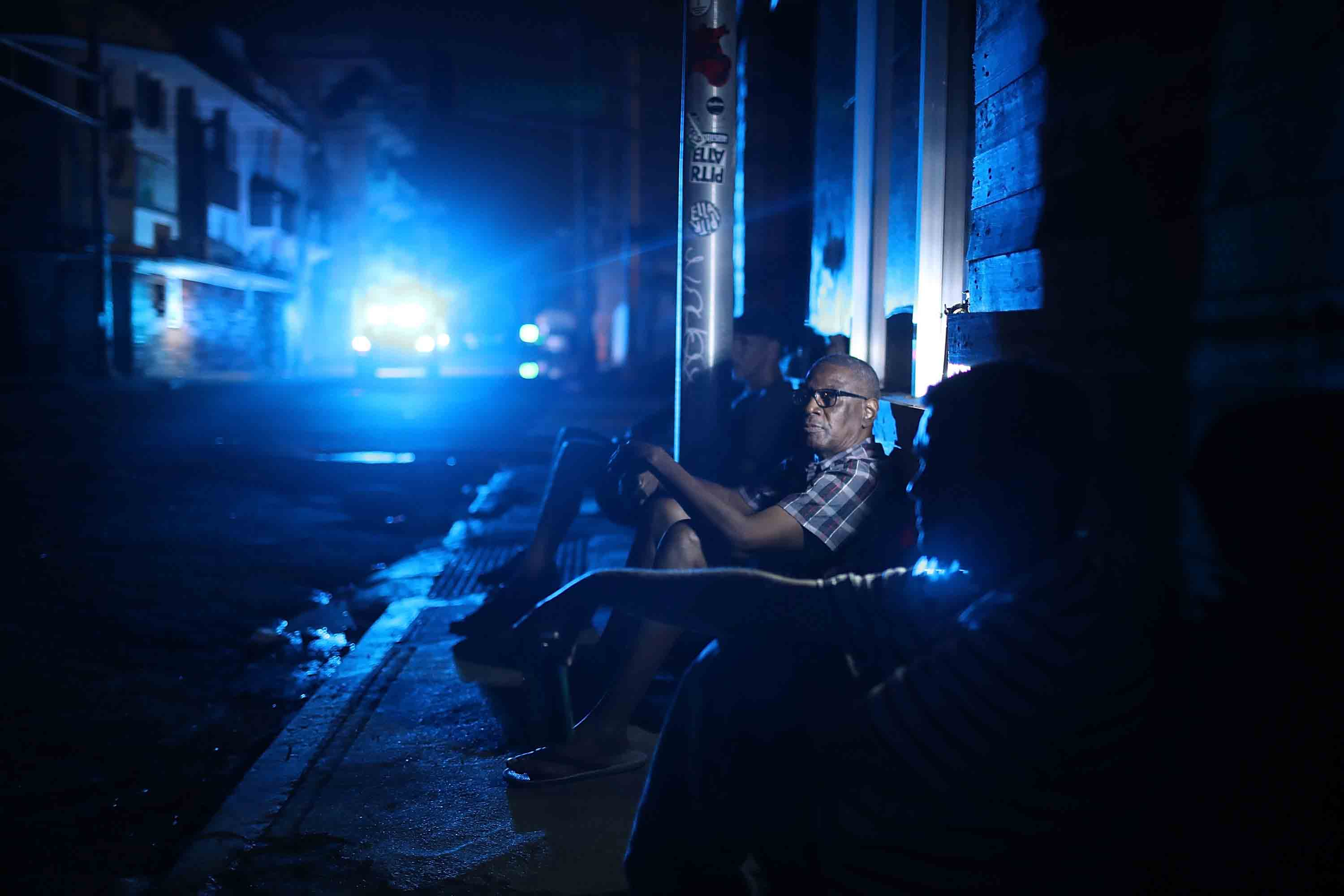 SAN JUAN, PUERTO RICO - SEPTEMBER 23: Jaime Degraff sits outside as he tries to stay cool as people wait for the damaged electrical grid to be fixed after Hurricane Maria.