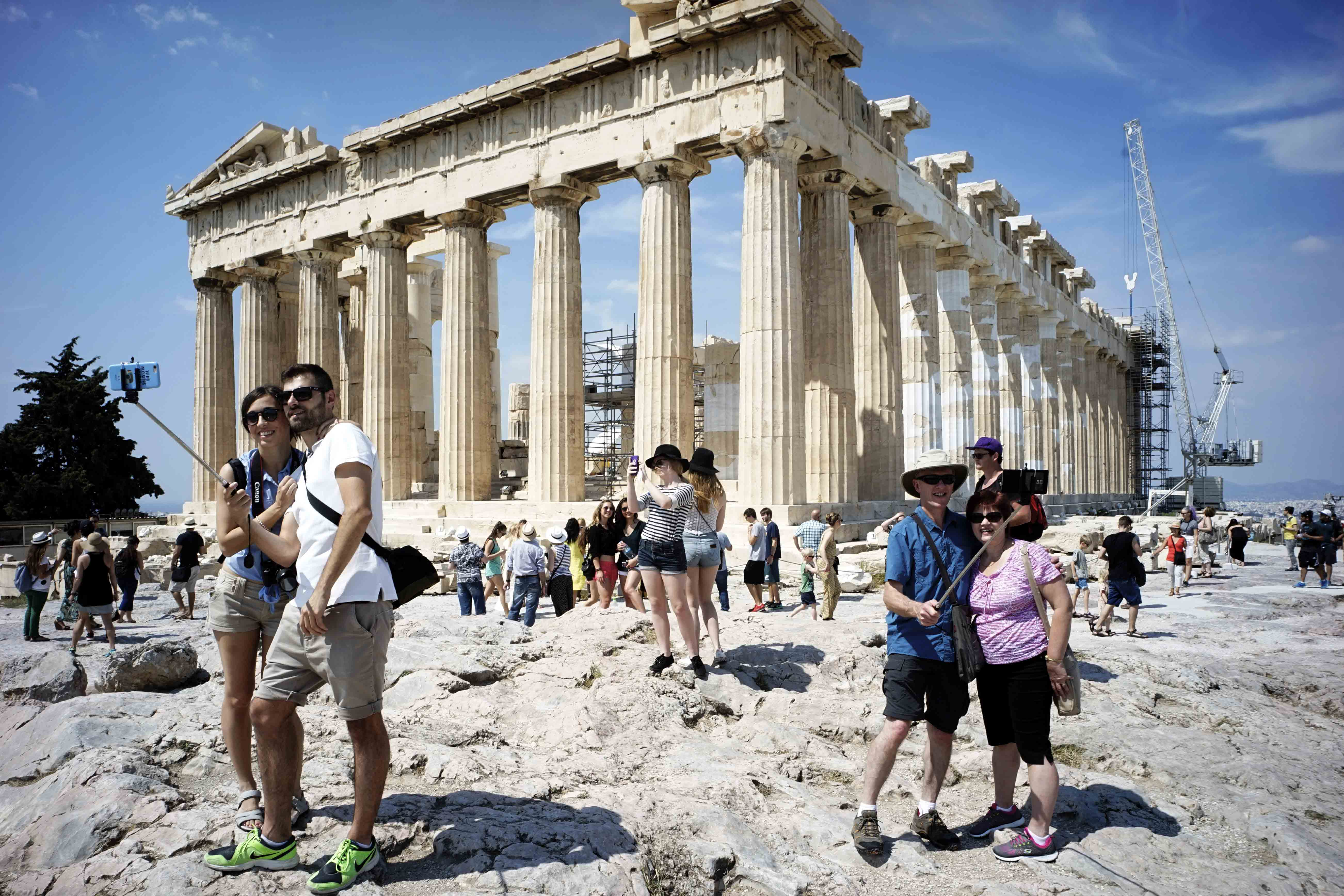Tourists taking selfies in front of the Acropolis in Greece.