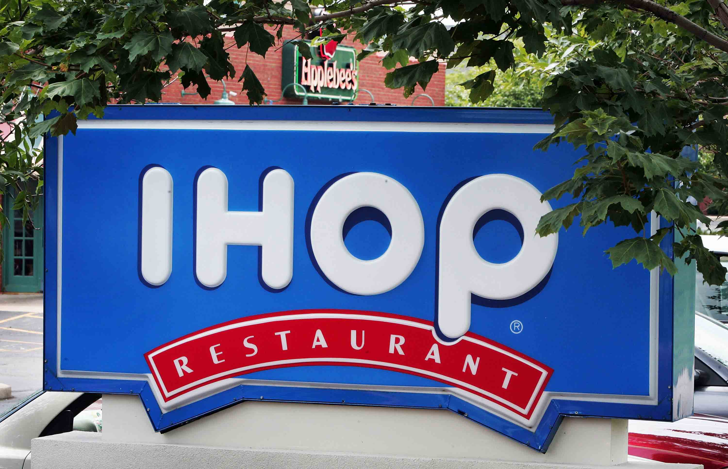 Signs mark the locations of neighboring IHOP and Applebee's restaurants in Elgin, Illinois.