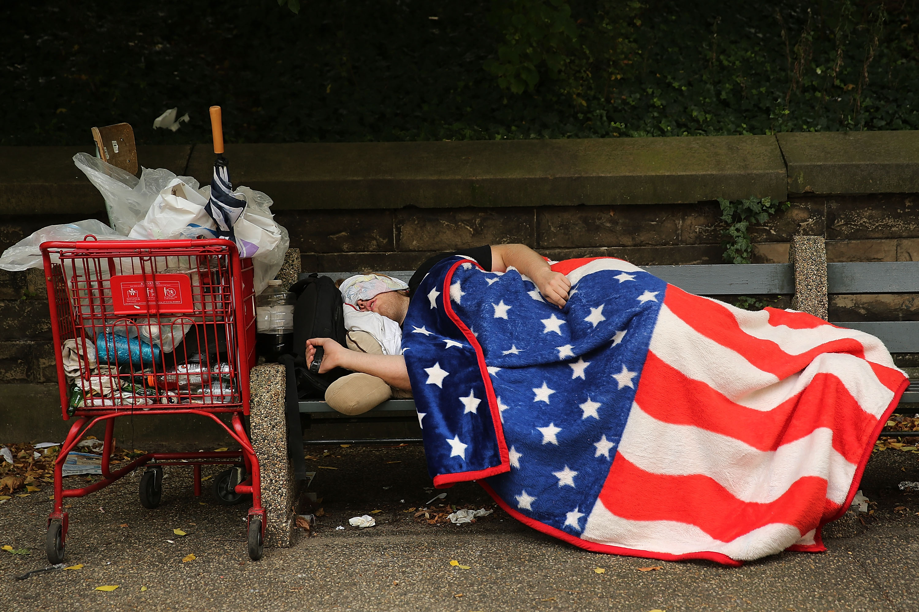 NEW YORK, NY - SEPTEMBER 10: A homeless man sleeps under an American Flag blanket on a park bench on September 10, 2013 in the Brooklyn borough of New York City. (Photo by Spencer Platt/Getty Images)